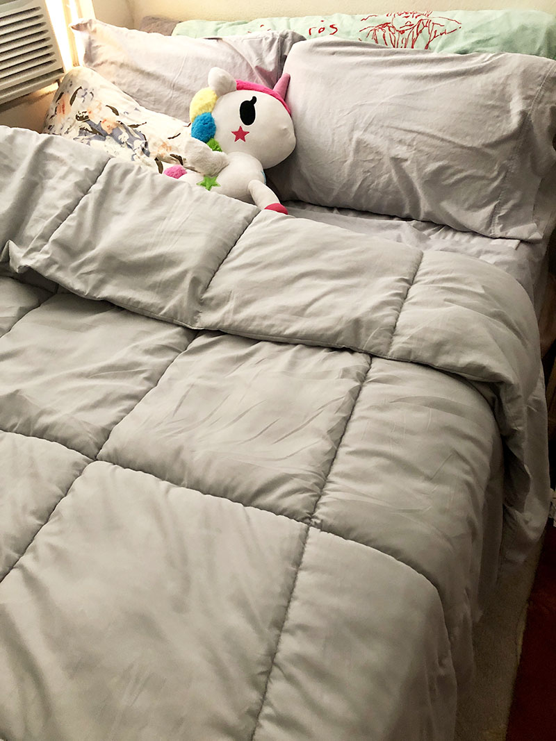 Fully made bed with gray GhostBed sheets, platinum Down Alternative Comforter, Tokidoki Unicorno plush, and Sigur Ros towel (for when I sleep with wet hair). There's also a body pillow with furry cover behind the pillows!